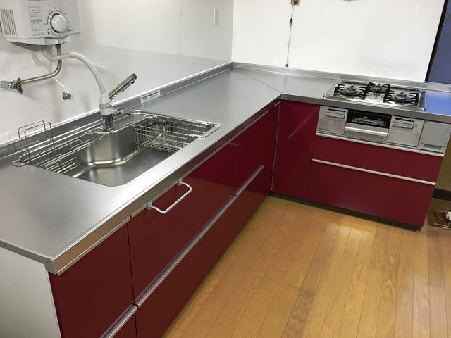 ワインレッドのパネルが美しいL型キッチン